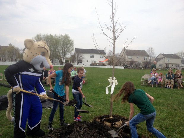 Dash, the Chicagoland Speedway mascot, helps fifth-graders from Wesmere School in Plainfield plant a tree outside the school on Monday during an early Arbor Day celebration.