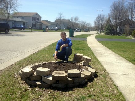 Jim Tieber, forester for Joliet, kneels over some dirt along a parkway in the Grand Prairie subdivision where an Ash tree was recently removed due to devastation from the Emerald Ash Borer.