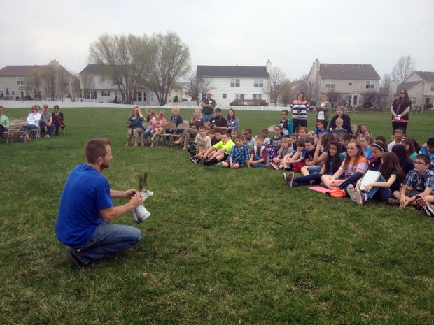 Jim Tieber, forester and certified arborist, teaches students from Wesmere School how to plant a tree during an Arbor Day celebration held Monday. Meanwhile, Tieber is expected to remove hundreds of trees this year throughout the city that have been infested by the Emerald Ash Borer.