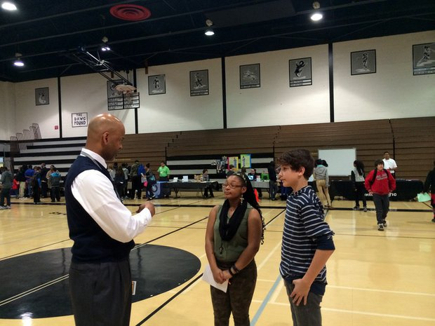 Brooks Middle School Keith Wood chats with students Asha Wilson and Tyler Bialek at Thursday's College & Career Fair.