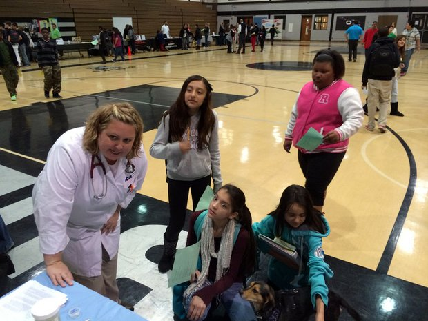VCA Bolingbrook Animal Hospital Veteranarian Juli Rowlett talks to students about the hospital while Penny, one of the dogs from the hospital, looks on.