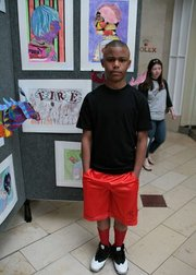 """Malique stands beside his drawing entitled """"Fire."""""""