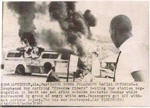 "Moses Newson outside of a ""Freedom Riders"" bus which was firebombed by an angry mob near Anniston, Alabama in 1961. Newson was among those aboard the bus during the attack."