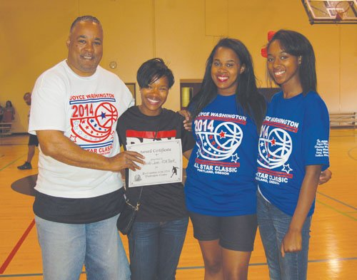 Joyce Washington Classic Director and Portland Observer Publisher Mark Washington, joins classic volunteers Quayana Washington and Shay Washington to present a donation from the charity game to Jenita Jones of the Portland Track Club.