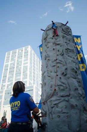 A 3-year old climbs this 25 foot rock-wall all by himself as friends, family and onlookers cheer him on. #HarlemWeek (08/17/2014)