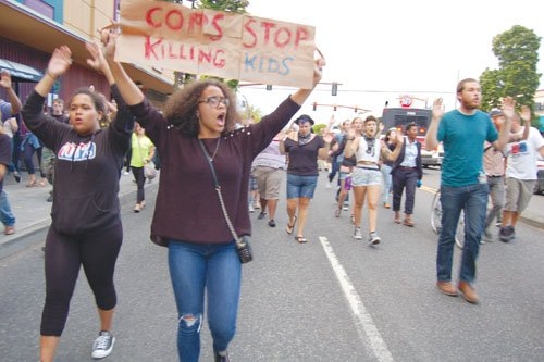The police shooting death of a black teenager halfway across the country have Portland residents raising their hands and voices ...
