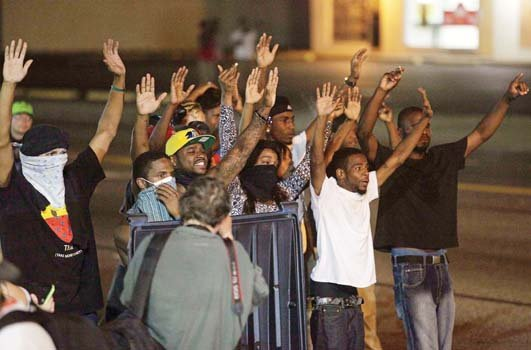 """Protesters of the shooting death of Michael Brown Jr. take the """"hands up, don't shoot"""" stance in Ferguson, Mo. as police point their weapons at them."""