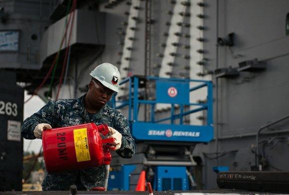 Aviation Boatswain's Mate (Equipment) 3rd Class Ladarius Myers, from Houston, fuels a flight deck tractor aboard Nimitz-class aircraft carrier USS ...