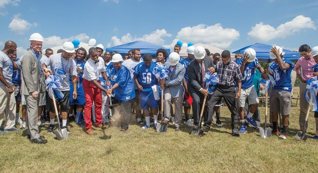 Schools and city officials and the John Marshall Justices dig in last Thursday for the ceremonial groundbreaking for the team's new football field. The project will start with placement of turf and will be ready for play next season.