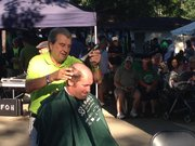 Joliet Mayor Tom Giarrante shaves a head during the St. Baldrick's Foundation fundraising event that was part of the Will County Celtic Fest in Joliet's St. Joseph Park.