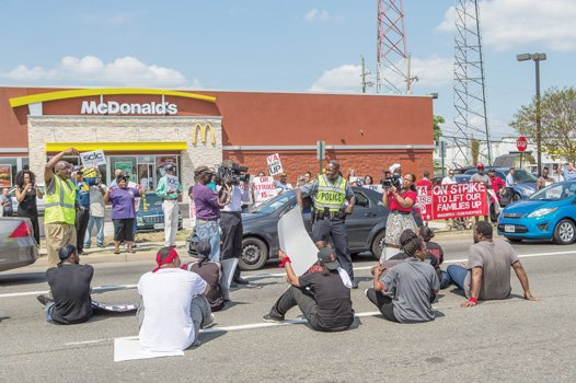 Fast food workers stage a sit-in on Mechanicsville Turnpike in front of the McDonald's. Their purpose: To highlight their demand for a hike in the $7.25 minimum wage. Fellow activists on the sidewalk hold up signs of support.