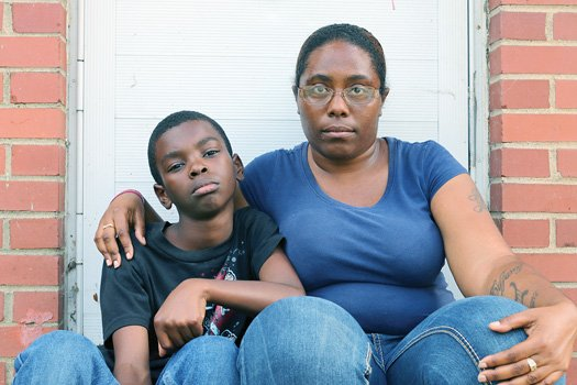 Javian Buffaloe sits with his mother, Tiffany, after returning home Tuesday from his first day of class at Martin Luther King Jr. Middle School.