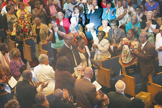 """Audience members stand in ovation Saturday honoring Richmond music icon Harold S. Lilly Sr. at an event commemorating his life and musical career as an organist. His daughter, Allison, escorts him through the appreciative crowd in the tribute titled, """"The Heart of a Servant."""""""