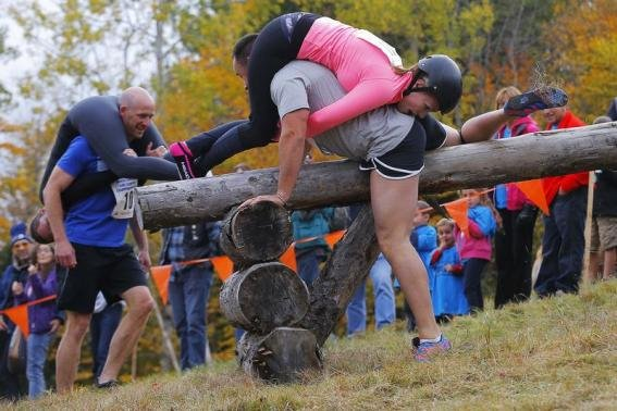 Men with their wives slung over their shoulders bounded over log hurdles and charged through a muddy pit on a ...