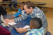 AARP Experience Corps volunteer member Doug Hebard reads to eight-year-old Raymond Bowman and seven years-old Tyon Matthews.
