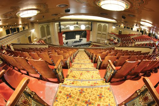 A balcony view shows upgraded, padded chairs in the 3,600-seat auditorium.
