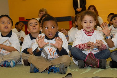 Holding tiger masks and seated on colorful reading rugs, pre-kindergarten students from John Ruhrah Elementary Middle School learned several words ...