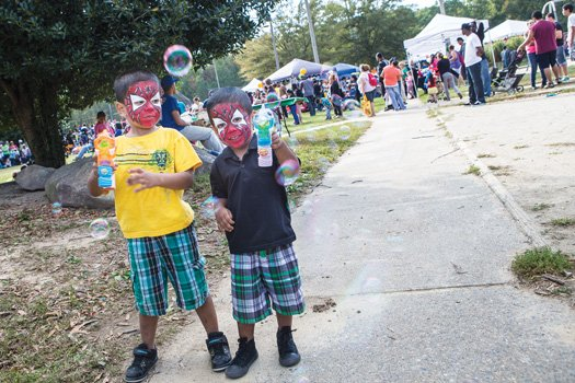 Christopher Bradley, left, and Caser Bradley make bubbles while wearing colorful face paint. They were among hundreds of people who enjoyed the 10th Annual Imagine Festival on Oct. 18. Location: Broad Rock Sports Complex on South Side. The event celebrates diverse communities with musical and dance performances, arts and crafts, food, sports and other activities.