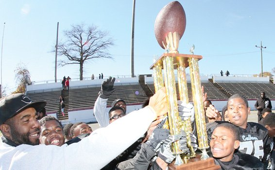 Above, the Calhoun Cougars raise their trophy at the Junior Division of Richmond Parks and Recreation Center Youth Football Tournament.