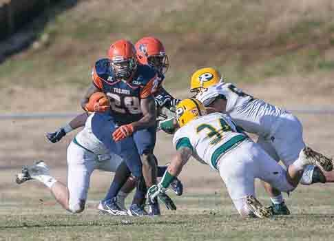 Virginia State University running back Kavon Bellamy pushes past Long Island University-Post defenders Saturday in Ettrick. The Trojans won, 28-17, moving to the second round in the NCAA playoffs.
