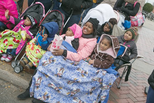 Parade-goers stay warm as they enjoy the array of floats, marching bands and even an appearance by Santa Claus.