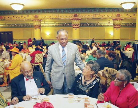 The host, Mayor Dwight C. Jones, greets partygoers at the Mayor's Senior Holly Ball. Location: The ballroom in the Altria Theater.
