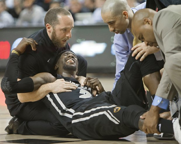 Virginia Commonwealth University basketball star Briante Weber grimaces as coach Shaka Smart, second from right, and others assist him moments after his injury during Saturday's game against the University of Richmond at the Siegel Center.