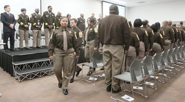 Jay'Neka Stancel proudly is pinned with a deputy's badge by her father, Carl White, at the Richmond Sheriff Office's first Basic Training Academy graduation ceremony last Friday at the new Richmond Justice Center. Class President Misha Goins leads her 22 classmates during the ceremony as Sheriff C.T. Woody Jr. and others watch from the stage.