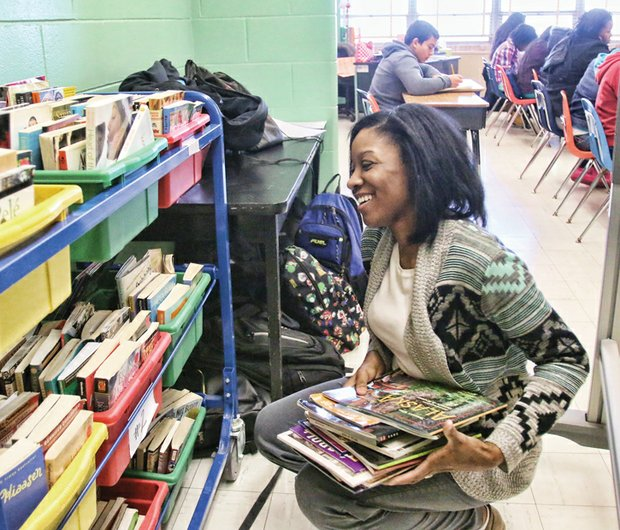 Teacher Cierra Claughton selects books for her seventh- grade English class at Clark Springs Elementary School Wednesday. She and other teachers, administrators and students made the transition this week into the West End elementary school after they were forced to move from Elkhardt Middle School in South Side because of a mold infestation.