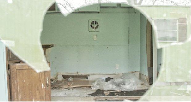 A view through a trailer's broken window shows the destruction inside.
