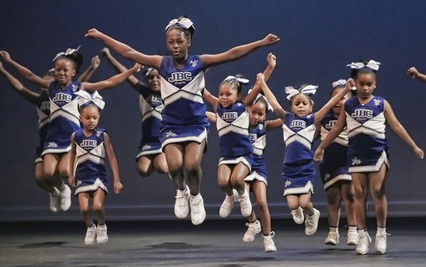 Cheerleaders from Richmond's John B. Cary Elementary School leap in mid-cheer during a routine performed Feb. 28 at Generation Dream 2015. Monty Jones also shows off his skills dancing to the rhythms of Drums No Guns. The music, spoken word, dance and arts event was hosted by the Richmond Peace Education Center to promote the ideals of Dr. Martin Luther King Jr. Location: Henrico Theater in Highland Springs.
