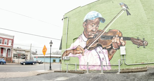 """Local artist Ed Trask wants his mural in the 1100 block of North 25th Street in Church Hill to say, """"Hey, look at this area. These lovely people are not getting the same chances the rest of us are receiving."""" Mr. Trask said he painted the mural, on his own time, to splash some color into the bleak landscape of the impoverished neighborhood. He wanted kids in the city's East End to know that the city loves them and to give the residents in """"sometimes forgotten certain areas ... a new sense of optimism through color and light."""" The mural was completed with help from local businesses and organizations, such as the Better Block initiative, a community effort to improve the safety and appeal of local neighborhoods. Mr. Trask said he hopes the mural will get people to see the area in a different light."""