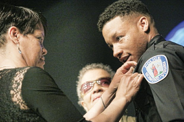 Newly sworn Richmond Police Officer Timberly Bolden, left, is pinned by his proud mother, Detral Bolden, as