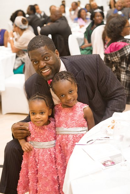 Robert W. Brown Jr. shares a treasured moment Sunday with his daughters, Kendell, 2, and Morgan, 4, at the Trinity Family Life Center on North Side.