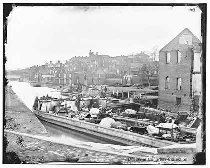 Newly liberated black people with all they own are packed onto a boat on Richmond's Kanawha Canal as the charred ruins of the city stand in the background in this photograph, circa April-June 1865.