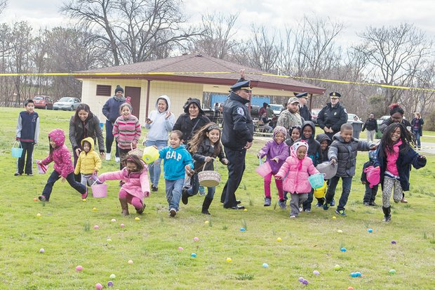 Children happily rush to collect plastic, candy-filled eggs at the Charlie D. Sydnor Playground on South Side. Police Chief Alfred Durham gave the signal to put the children in motion at the pre-Easter event last Saturday at the public playground and park. Location: 15th and Maury streets. This was the third year for the event hosted by the group Putting Communities Together.