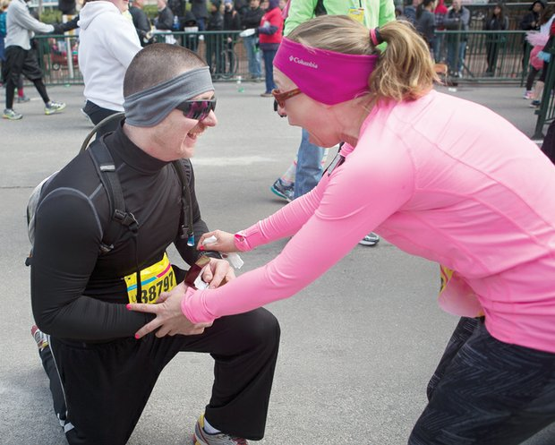 """Give Brian McGee an """"A"""" for originality in proposing marriage at the Monument Avenue 10K race last Saturday. First, he drops to his knee to propose to Jennifer Lane after they crossed the finish line near Monroe Park."""