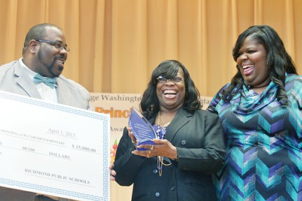"""Carver Elementary School Principal Kiwana S. Yates, right, is all smiles as she is celebrated during a school assembly Wednesday for winning a 2015 R.E.B. Award for Distinguished Educational Leadership. She was one of four Richmond area principals to be honored by the R.E.B. Foundation in partnership with The Community Foundation. Mrs. Yates was joined by her husband, Darnell Yates, and her mother, Patricia Evans-Branch, at the assembly, where she was presented with a check for $15,000. Half of that is for her personal use. The other $7,500 will be used for educational field trips, she said. """"I was very excited and surprised,"""" Mrs. Yates told the Free Press of the ceremony. """"The fact that the staff and students were able to pull off such a wonderful event was priceless. This made my heart melt."""""""