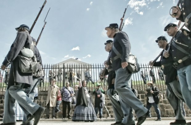 Re-enactors representing the United States Colored Troops triumphantly march Saturday along Bank Street.