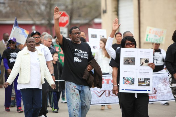 Pastor Lonnie Posley (center) participates in the Men of Valor 2's second prayer walk to end gun violence in Joliet.