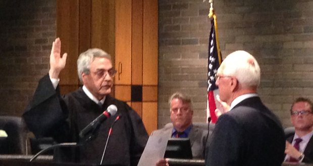 Will County Circuit Judge Jeff Allen swears in Pat Muldron, the newly elected councilman for District 2. Council members Larry Hug (center) and Jim McFarland (far right) observe.