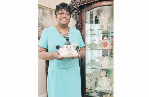 The Rev. Jeanette Brown displays one of the more than 100 colorful teapots at Harriet's Place, the North Side home of Scripture Tea Fellowship Ministries.