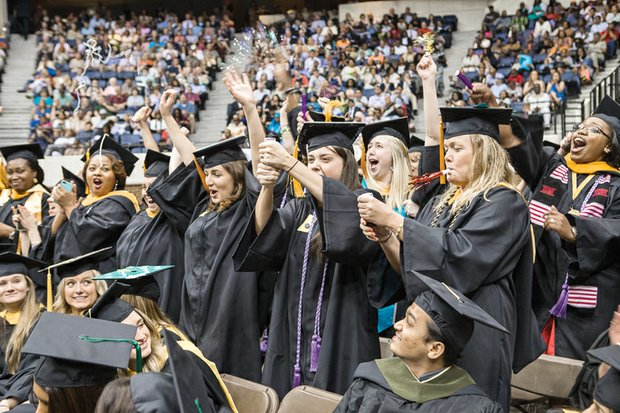 Members of the Virginia Commonwealth University Class of 2015 celebrate with confetti, noisemakers and cheering during Saturday's commencement at the Richmond Coliseum.
