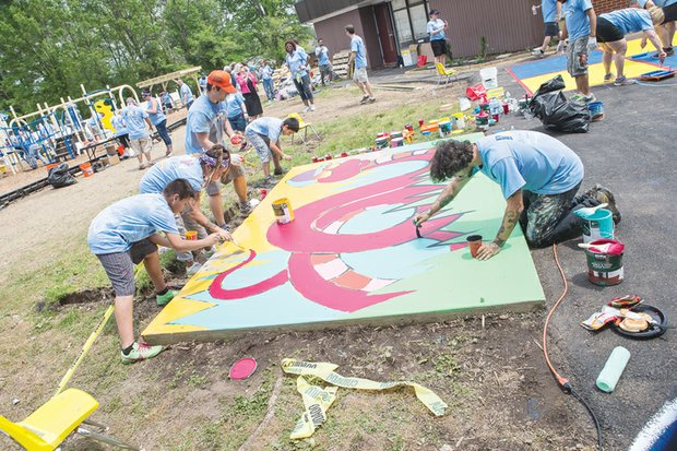 """Volunteers paint a colorful mural at a new playground they built May 7 at Elizabeth D. Redd Elementary School on South Side to honor the memory of Martin """"Marty"""" Cobb, who was a first-grader at the school."""
