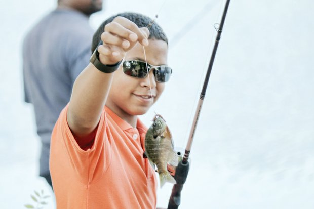 Melvin Oliver, 11, shows off the bluegill he caught Saturday in Shields Lake during the Family Fishing Fair in Byrd Park