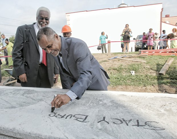 TOPPING OFF HISTORY -Dr. Leonard Edloe,  a member of the museum's board of directors, watches as former museum CEO Stacy L. Burrs, right, signs his name on the last beam that will be placed atop the building at 122 W. Leigh St. in Jackson Ward. Mr. Burrs currently serves on the museum board and is overseeing construction of the $8 million project at the site