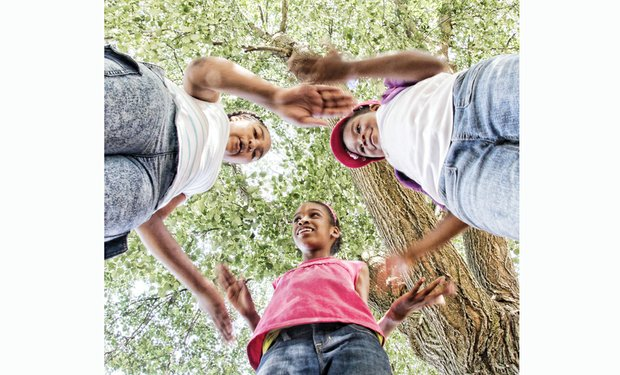 "SUMMER FUN- Friends happily play a three-way version of the hand game ""Hesitation"" in Abner Clay Park in Jackson Ward. They are, from left, Tonye Fox, 11; Lucy Stancell, 10; and Kyndal Caleb, 5. In the game, one person rests hands palms down atop the upturned palms of another. The person whose hands are on top quickly tries to move their hands before they are slapped by the person whose hands are on the bottom."