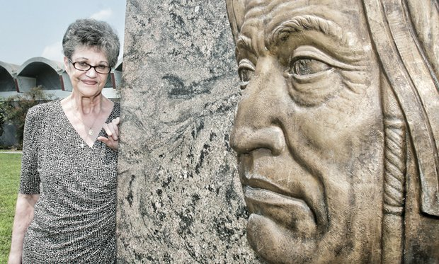 """Joyce """"Pale Moon"""" Krigsvold, a volunteer at the Pamunkey Indian Museum and Cultural Center on the reservation and an expert potter, stands near a likeness of the first Pamunkey chief, Powhatan, on the tribal grounds in King William County."""