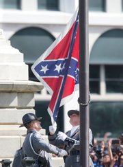 A South Carolina Highway Patrol honor guard removes the Confederate flag from the Columbia statehouse grounds during a ceremony witnessed by thousands.
