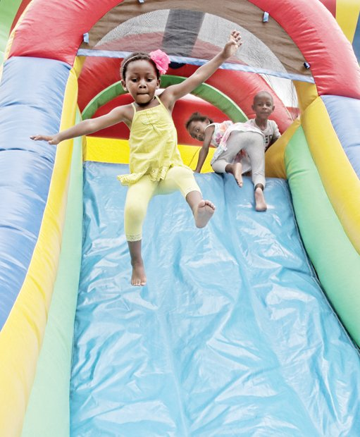 ONE GIANT LEAP- All eyes are on 3-year-old Gabrielle Ba as she sails through the air and down a slide. She and her playmates were having fun Saturday at the 2nd Annual Brookland Park Boulevard History Festival on North Side. The free community event attracted hundreds of people and included entertainment, a farmer's market, health screenings and lots of food and fun. Please see additional photos on B1.